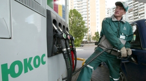 File photo of a worker filling up a car at a Yukos gas station in Moscow