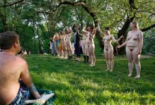 "A spectator watches as the all-female cast of the Outdoor Co-Ed Topless Pulp-Fiction Appreciation Society theater company celebrates together following the company's production of Shakespeare's ""The Tempest,"" in Central Park, Thursday, May 19, 2016, in New York. 13 actors, dancers and musicians perform a ""stripped down"" version of the Shakespearean play using nudity to dramatize the conflict between the visitors to Prospero's island and its inhabitants. (AP Photo/Kathy Willens)"